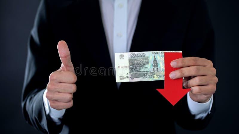 Hombre de negocios que sostiene los billetes de banco de la rublo rusa que muestran los pulgares para arriba, el caer de la flech foto de archivo