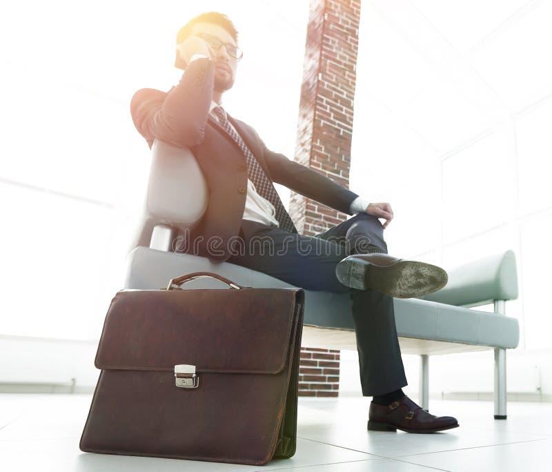 Hombre de negocios que sostiene su cartera en oficina fotografía de archivo