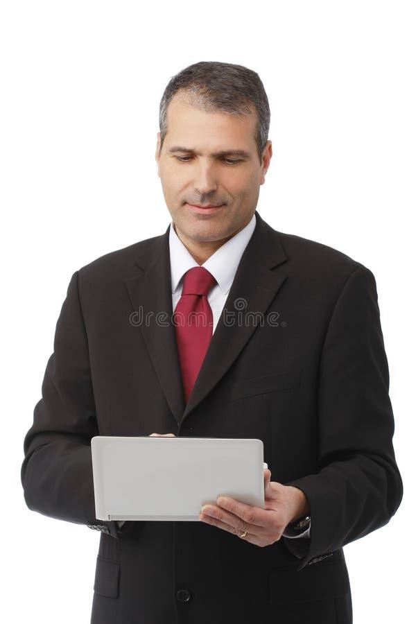 Hombre de negocios que sostiene su computadora portátil imagen de archivo