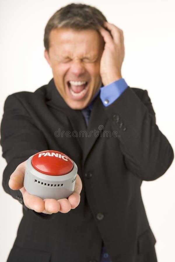 Hombre de negocios que sostiene un botón de pánico fotos de archivo libres de regalías