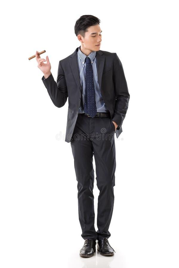 Hombre de negocios que sostiene un cigarro imagen de archivo libre de regalías