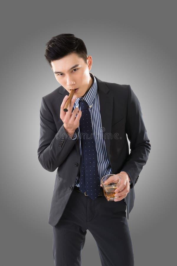 Hombre de negocios que sostiene un cigarro foto de archivo libre de regalías