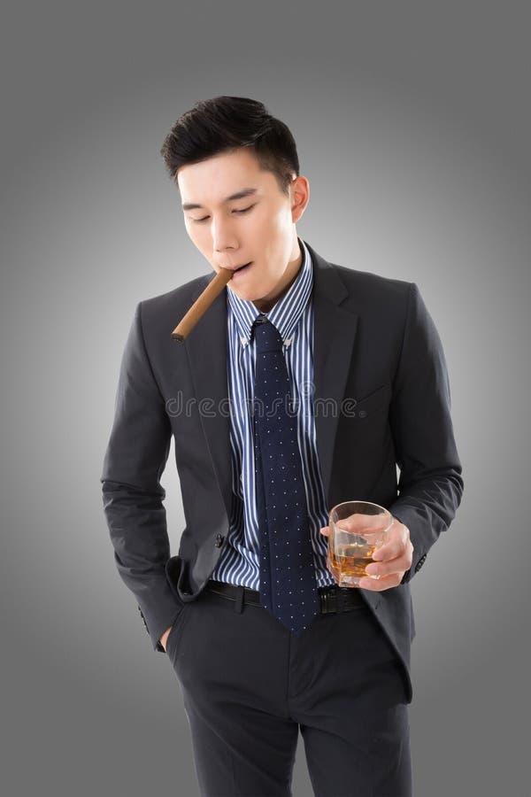Hombre de negocios que sostiene un cigarro fotografía de archivo libre de regalías