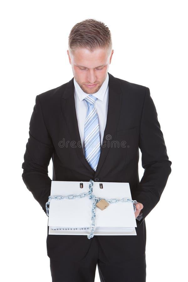 Hombre de negocios que sostiene un fichero de alto secreto imagen de archivo