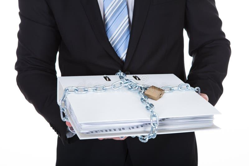 Hombre de negocios que sostiene un fichero de alto secreto foto de archivo