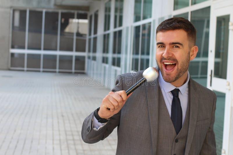 Hombre de negocios que sostiene un micrófono en espacio de oficina foto de archivo