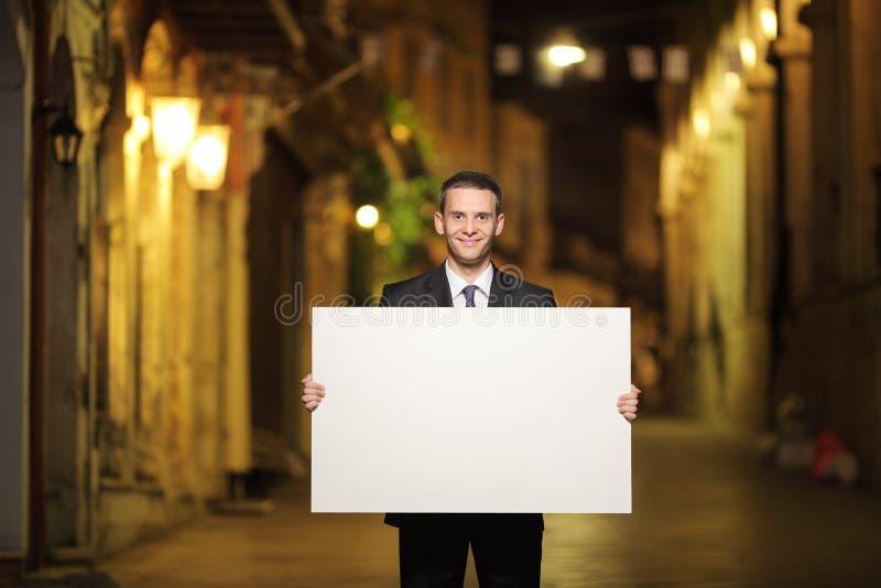 Hombre de negocios que sostiene un panel en una calle de la ciudad fotos de archivo libres de regalías