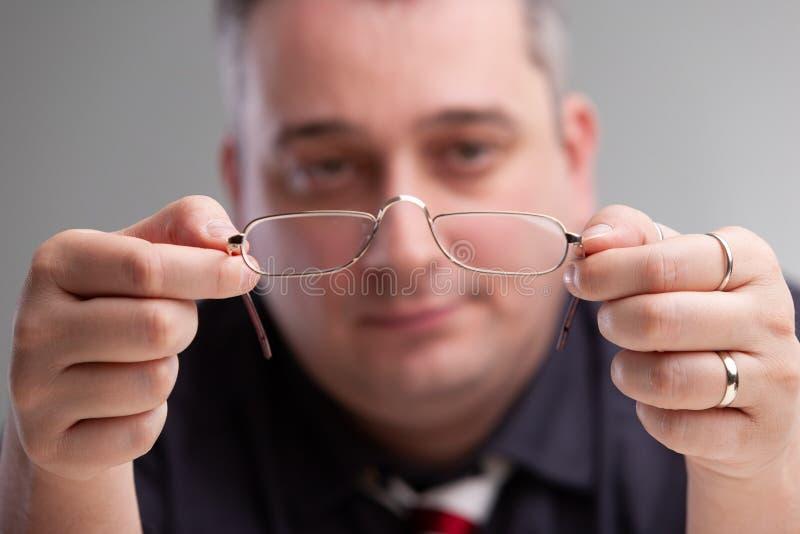Hombre de negocios que sostiene un par de lentes foto de archivo