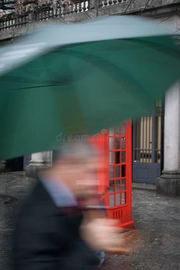 Hombre de negocios que sostiene un paraguas a toda prisa que pasa un telepho rojo imagenes de archivo
