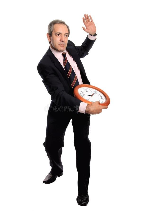 Hombre de negocios que sostiene un reloj fotos de archivo