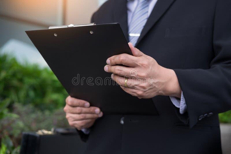 hombre de negocios que sostiene un tablero para trabajar en al aire libre imagen de archivo libre de regalías