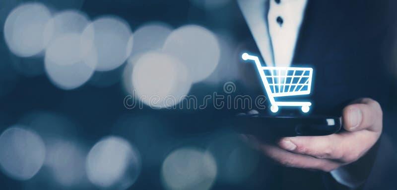 Hombre de negocios que sostiene un teléfono con un icono de las compras Compras en línea foto de archivo