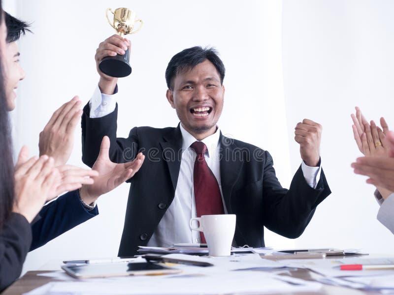 Hombre de negocios que sostiene un trofeo del oro equipo feliz y acertado del negocio recompensado por en la oficina imagenes de archivo
