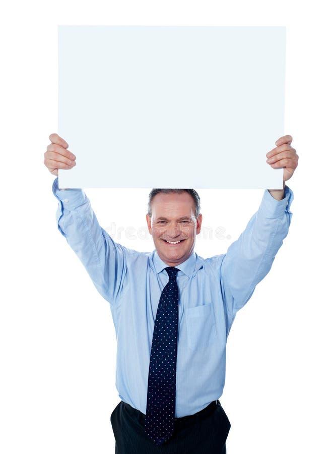 Hombre de negocios que sostiene una cartelera en blanco imagen de archivo libre de regalías