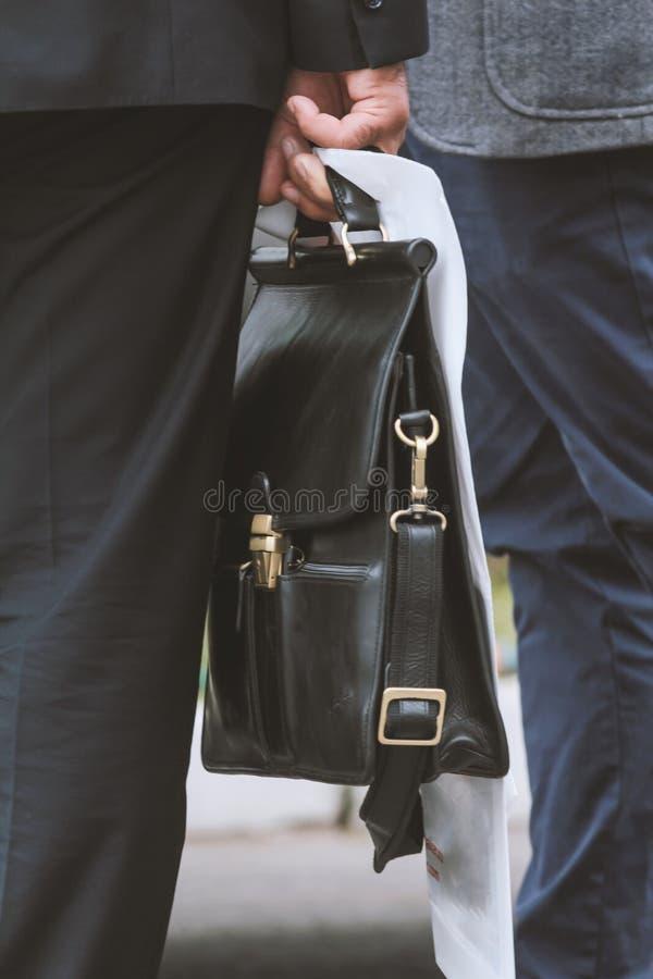 Hombre de negocios que sostiene una cartera disponible imagen de archivo