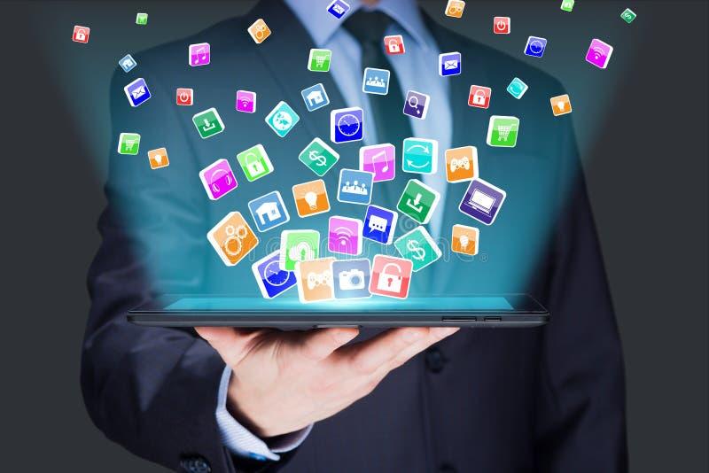Hombre de negocios que sostiene una PC de la tableta con los iconos de las aplicaciones móviles en la pantalla virtual Internet y fotos de archivo libres de regalías