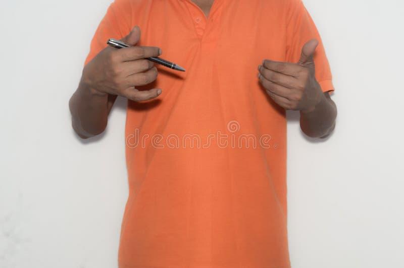 Hombre de negocios que sostiene una pluma en su mano, explicando una estrategia de marketing imagen de archivo libre de regalías