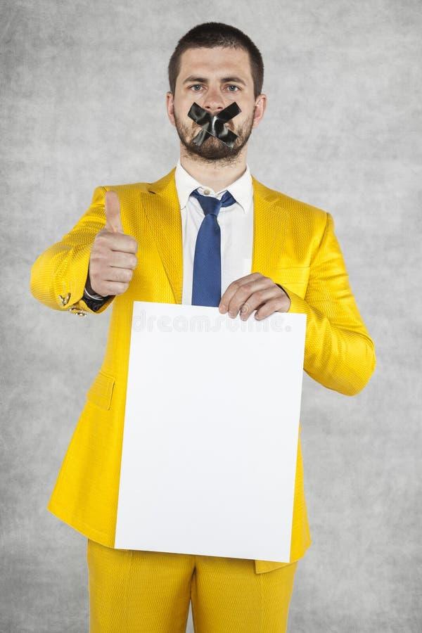 Hombre de negocios que sostiene una tarjeta en blanco, pulgar que destaca foto de archivo