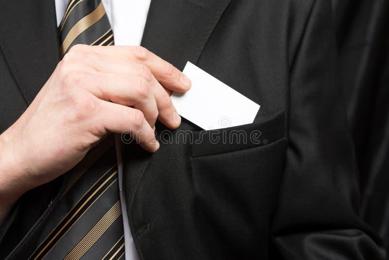 Hombre de negocios que sostiene una tarjeta fuera de su bolsillo del juego fotos de archivo libres de regalías