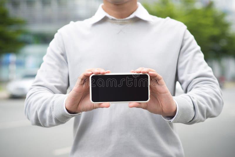 Hombre de negocios que sostiene y que muestra la pantalla del teléfono elegante fotografía de archivo libre de regalías
