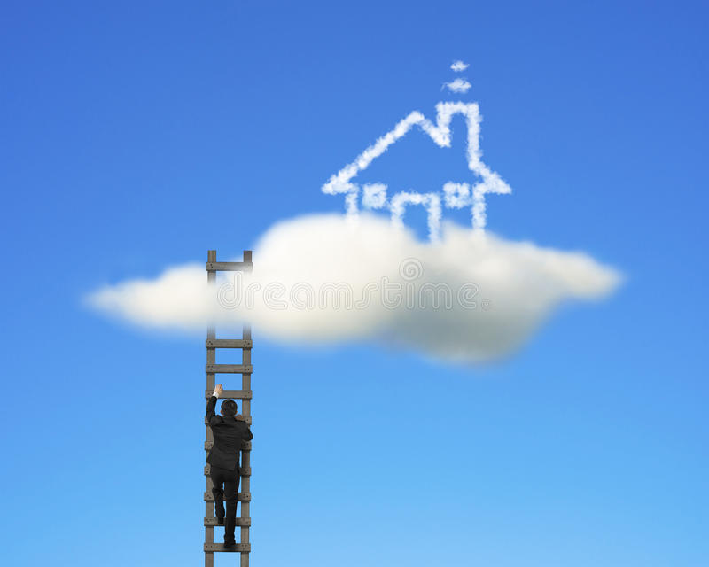 Hombre de negocios que sube en escalera de madera para alcanzar la casa de la nube imagenes de archivo