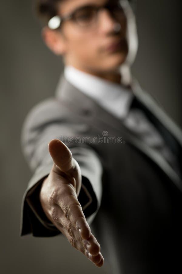 Hombre de negocios que sube hacia fuera su mano para sacudir el suyo imágenes de archivo libres de regalías