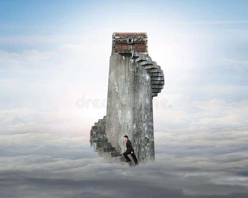 Hombre de negocios que sube la escalera espiral hacia cofre del tesoro en t imagen de archivo