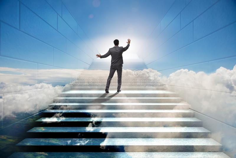 Hombre de negocios que sube la escalera para arriba estimulante de la carrera en el negocio co foto de archivo