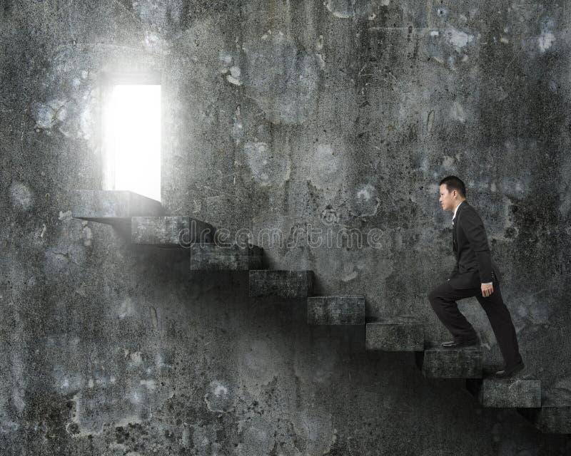 Hombre de negocios que sube las escaleras concretas hacia puerta con el lig brillante imagen de archivo