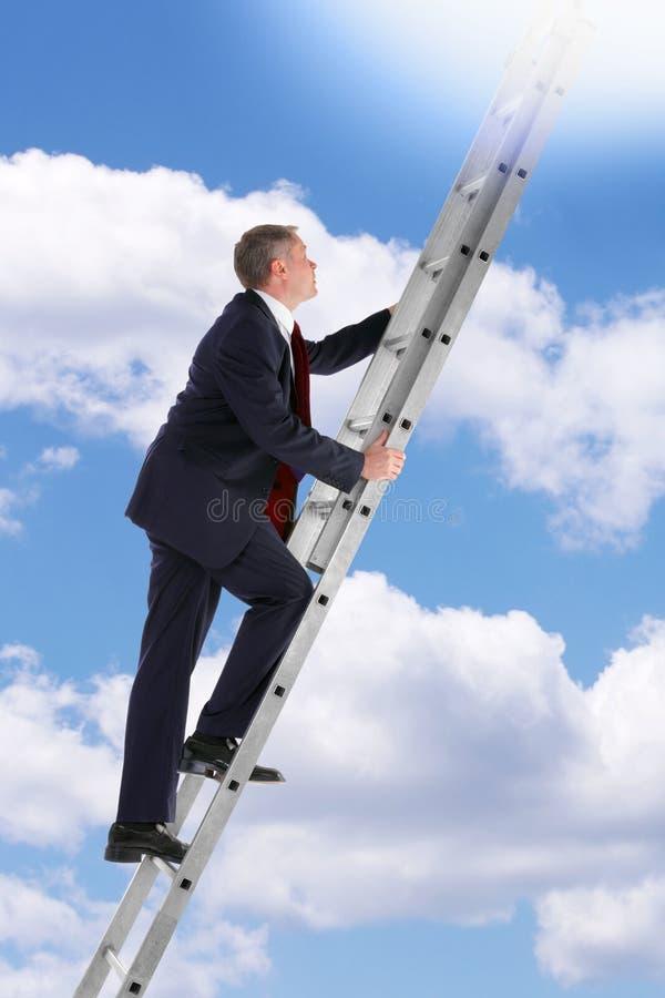 Hombre de negocios que sube una escala en el cielo foto de archivo libre de regalías