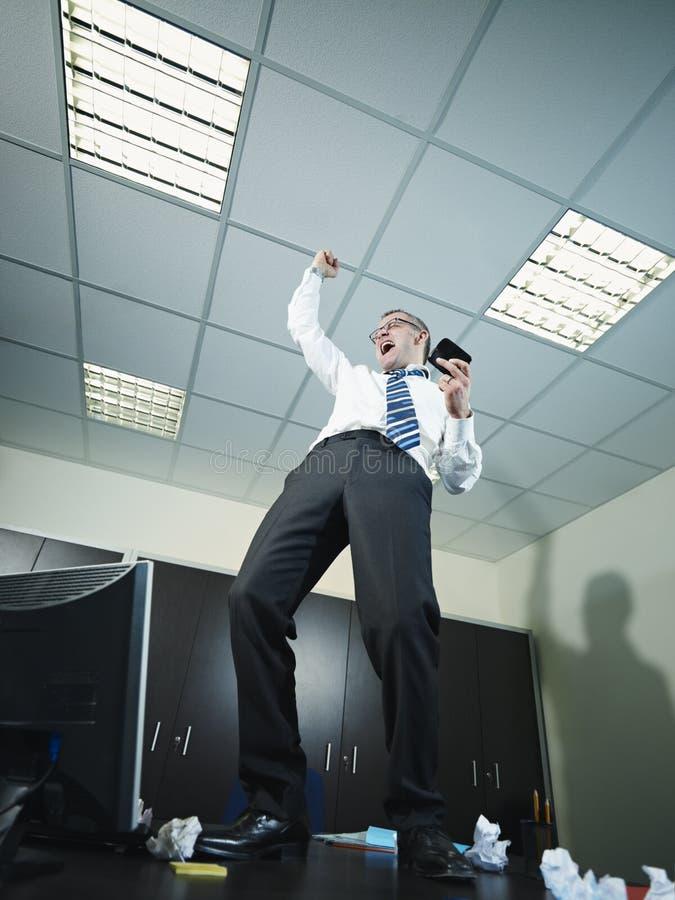 Hombre de negocios que tiene buenas noticias en el teléfono imágenes de archivo libres de regalías