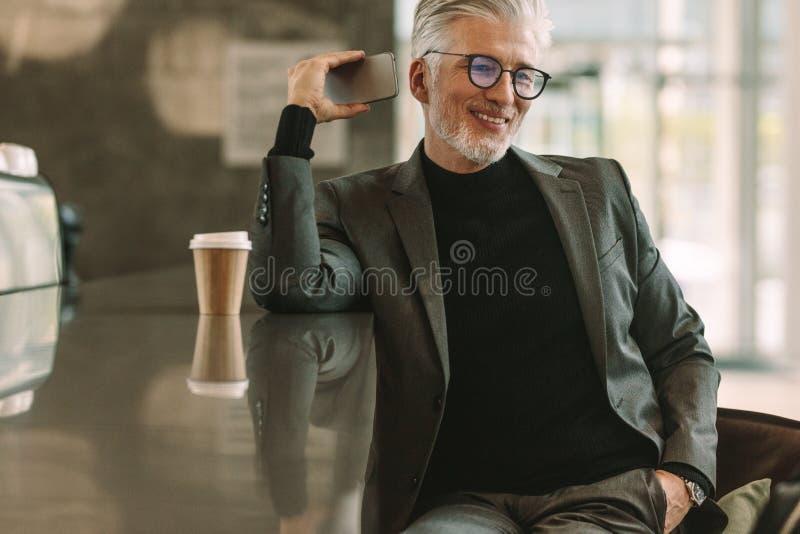 Hombre de negocios que tiene conversación sobre el teléfono en café imagenes de archivo