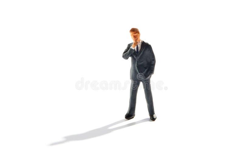 Hombre de negocios que tiene dudas que se colocan de reflexión imagen de archivo