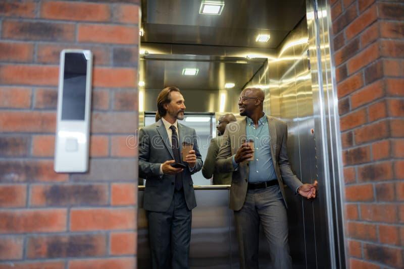 Hombre de negocios que tiene pequeña charla en el elevador por la mañana fotografía de archivo libre de regalías