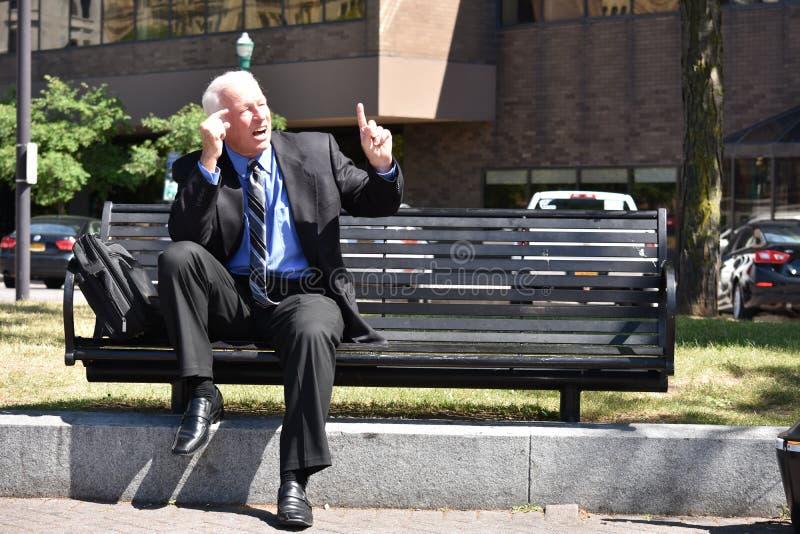 Hombre de negocios que tiene una idea que se sienta en banco imágenes de archivo libres de regalías
