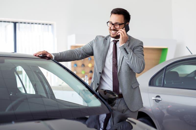 Hombre de negocios que tiene una llamada de teléfono en la sala de exposición del coche fotografía de archivo libre de regalías