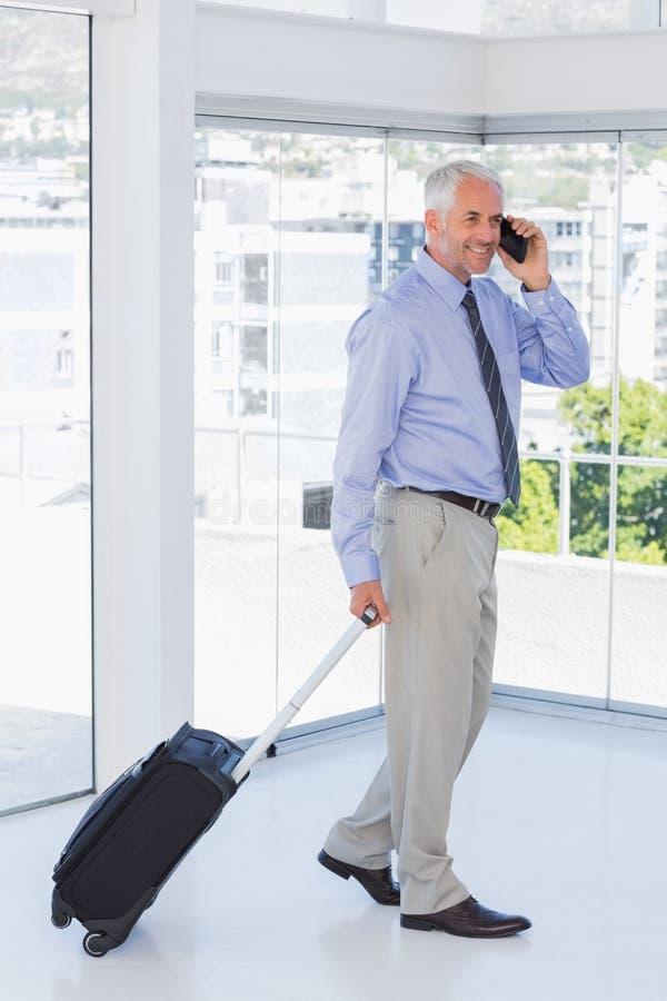 Hombre de negocios que tira de la maleta y que habla en el teléfono imágenes de archivo libres de regalías