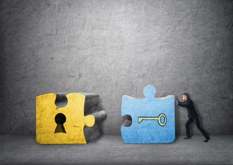 Hombre de negocios que tira juntos de pedazos de la llave y del ojo de la cerradura de rompecabezas imagen de archivo