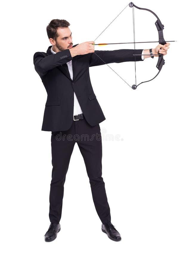 Hombre de negocios que tira un arqueamiento y una flecha foto de archivo libre de regalías