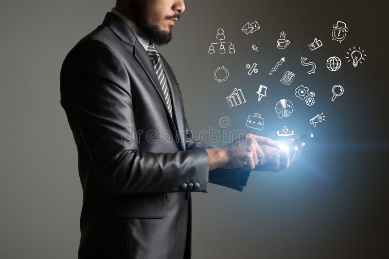 Hombre de negocios que toca en la pantalla del smartphone con el icono de los medios del garabato imagenes de archivo