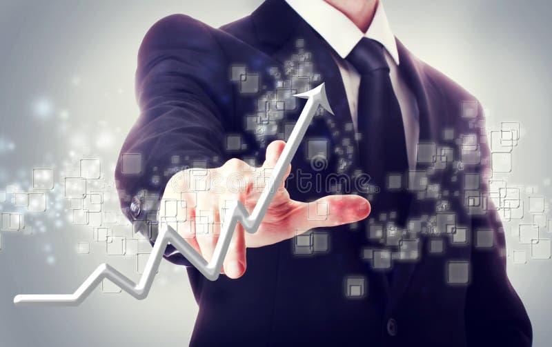 Hombre de negocios que toca una flecha de levantamiento foto de archivo libre de regalías