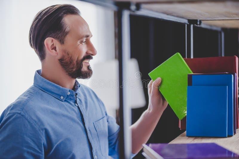 Hombre de negocios que toma el cuaderno del estante imagen de archivo libre de regalías