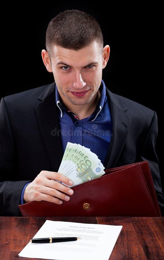Hombre de negocios que toma el soborno foto de archivo