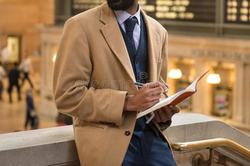 Hombre de negocios que toma la nota usando la chaqueta y el traje de negocios de la cachemira de la pluma que llevan y de la libr fotografía de archivo