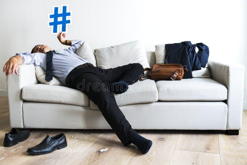 Hombre de negocios que toma la rotura que pone en el sofá fotos de archivo libres de regalías