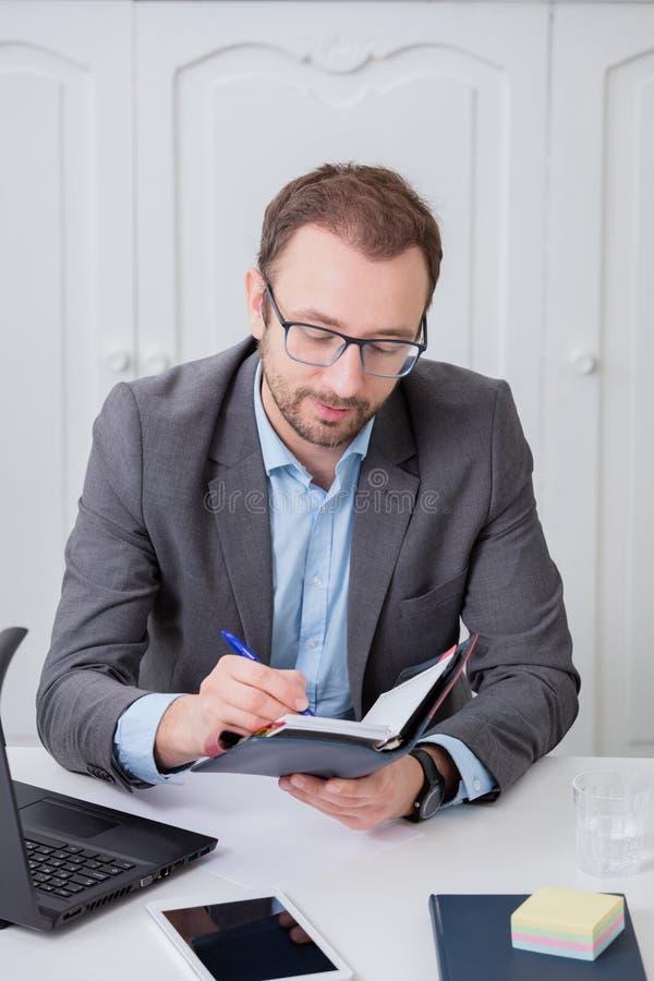 Hombre de negocios que toma notas en su escritorio fotografía de archivo
