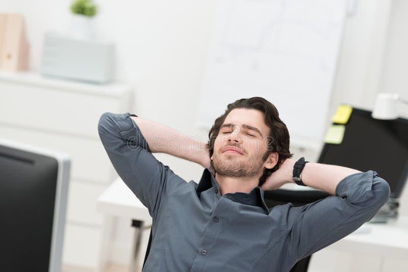 Hombre de negocios que toma una rotura en su escritorio foto de archivo libre de regalías