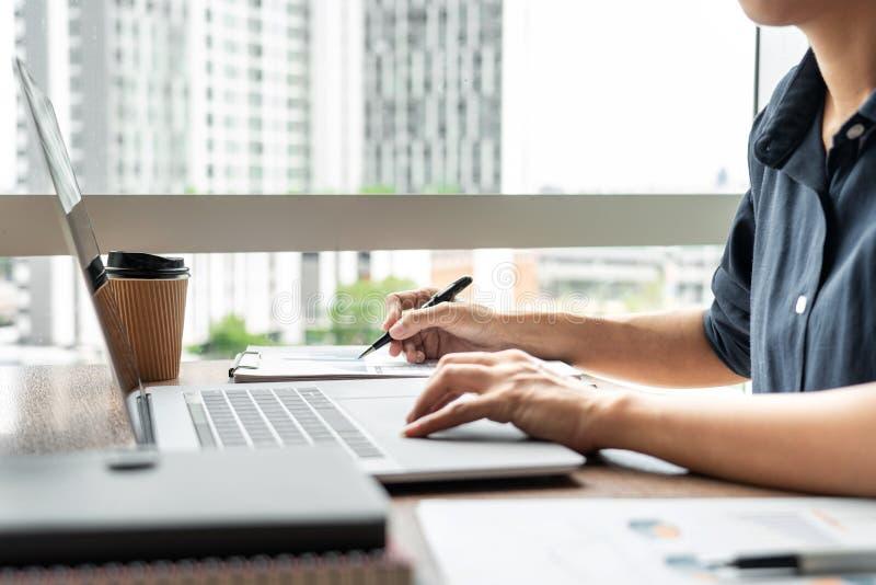 Hombre de negocios que trabaja con datos del gráfico en ordenador portátil y documentos en su escritorio en la oficina imagenes de archivo