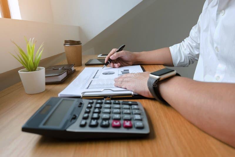 Hombre de negocios que trabaja con el documento de la declaraci?n de renta en la tabla de madera Concepto del asunto foto de archivo