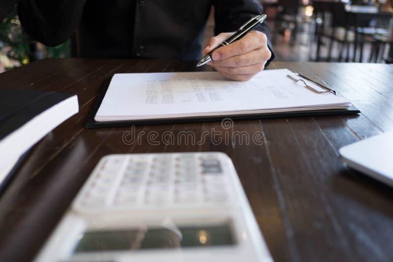 Hombre de negocios que trabaja con el documento de la declaraci?n de renta en la tabla de madera Concepto del asunto imágenes de archivo libres de regalías